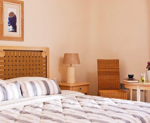 Bed, chair, bed table and lamp at Harmony Boutique Hotel view rooms.