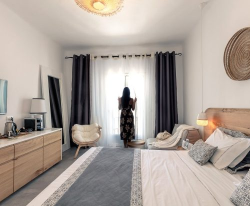 Lady beside the window, double bed and stylish furniture at Superior Rooms in Harmony Hotel.