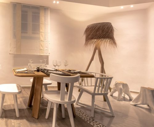 Stylish dining table, chairs and floor lamp at Harmony Boutique Hotel Amvrosia Restaurant.